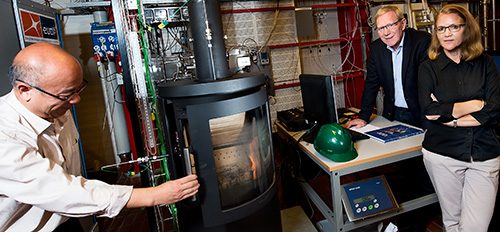 In the test hall, the stoves are fired under controlled conditions using online measurements of the most essential process parameters as well as the O2, CO, CO2, NOx, SOx gas components and volatile organic compounds in the flue gas. Particle emissions are also measured. (L – R): DTU researcher Weigang Lin, HWAM founder Vagn Hvam Pedersen, and DTU project leader Jytte Boll Illerup. (Photo: Joachim Rode.)
