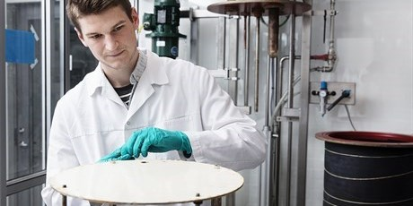 PhD student Victor Møller fixating a coating sample, for immersion into the acid-containing reactor in the background. Photo by Thorkild Christensen.